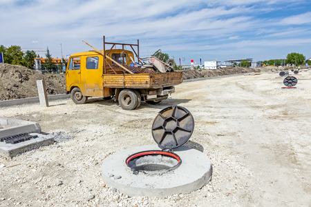 View on assembled new manhole with opened metal cover at construction site.
