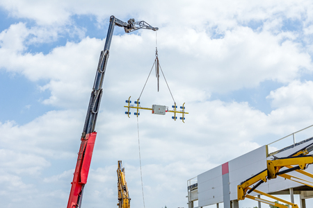 Telescopic mobile crane has elevated beam, tool hang on chain against cloudy sky.