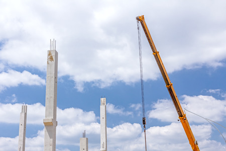 Crane arm is operating to assembly concrete pillars on new edifice. Stock Photo