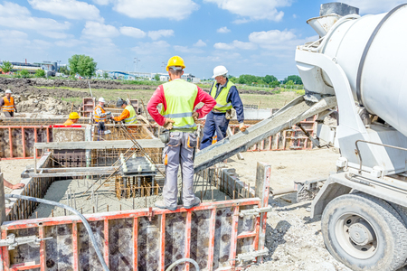 rigger: Zrenjanin, Vojvodina, Serbia - May 29, 2015: Workers at building site are pouring concrete in mold from mixer truck. Editorial