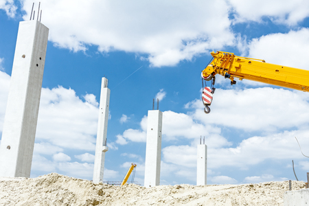 Crane arm is ready for operating to assembly concrete pillars on new edifice. Stock Photo