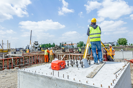 Zrenjanin, Vojvodina, Serbia - May 25, 2015: Surveyor engineer is measuring level on construction site. Surveyors ensure precise measurements before undertaking large construction projects. 스톡 콘텐츠