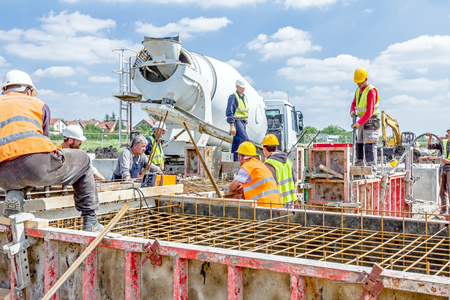 Zrenjanin, Vojvodina, Serbia - May 29, 2015: Workers at building site are pouring concrete in mold from mixer truck. Editorial