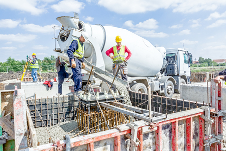 Zrenjanin, Vojvodina, Serbia - May 29, 2015: Workers at building site are pouring concrete in mold from mixer truck. Publikacyjne