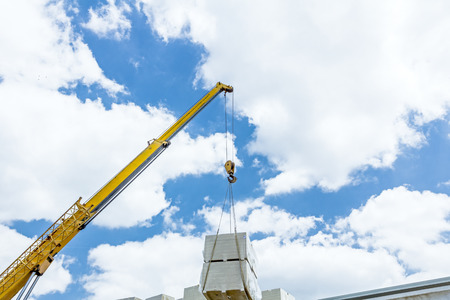 Mobile crane is loading cargo. View on construction site with machinery, people at work.  Stock Photo