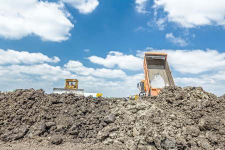 manage transportation: View on heavy bulldozer while he moving, leveling ground at construction site.  Heavy wheels are working at construction site. Stock Photo