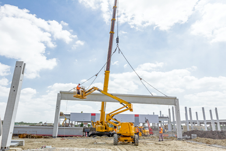 Mobile crane is operating and worker is assembly concrete joist in high place. Height worker is placing truss on building skeleton. Reklamní fotografie