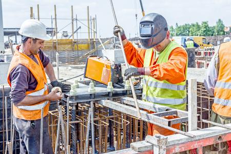Zrenjanin, Vojvodina, Servië - 29 mei 2015: Industrieel schot van de bouwvakkers die het lassen van metalen frame, kooi van de armatuur binnenkant van demontabele houten mal voor het betonneren pijler basis.