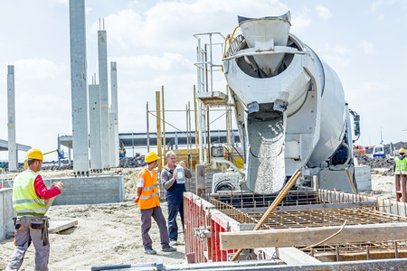 Zrenjanin, Vojvodina, Serbia - May 29, 2015: Workers at building site are pouring concrete in mold from mixer truck. 報道画像