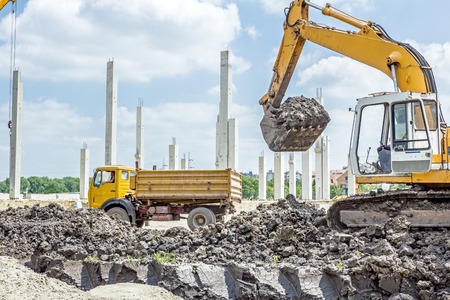 manage transportation: Big excavator is filling a dump truck with soil at construction site, project in progress. Stock Photo