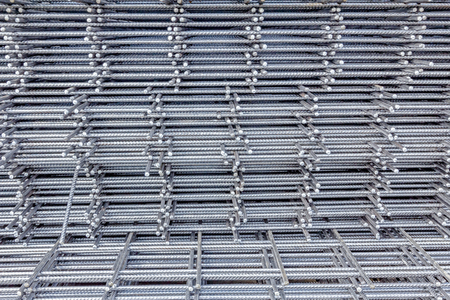 distributed: Spikes of rebar grid, reinforcing mesh, steel bars stacked for construction. Stock Photo