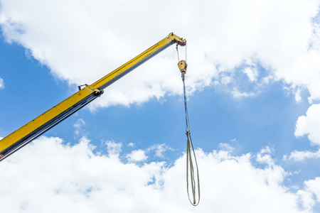 Telescopic mobile crane has elevated beam, rope and hook against blue sky.