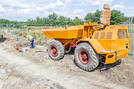 Little construction dumper carrier is at building site. Editorial