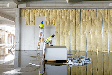 rock wool: Workers are assembly gypsum wall. Plasterboard is under construction using wooden ladder.