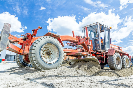Zrenjanin, Vojvodina, Serbia - June 29, 2015: Low angle view on red grader until is leveling ground at building site. Editorial