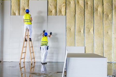 Los trabajadores son pared de montaje de yeso. Placas de yeso está en construcción usando escalera de madera.