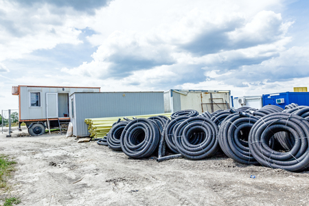 Makeshift storage material, HDPE and PVC pipe for different usage at construction site in the improvised warehouse. Stock Photo