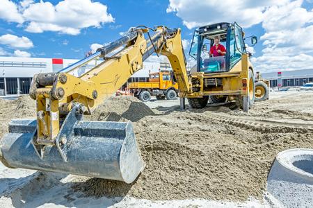 cargador frontal: Zrenjanin, Vojvodina, Serbia - Junio ??29, 2015: Excavadora amarilla está haciendo pila de suelo tirando hacia arriba en el montón de tierra en el sitio de construcción, proyecto en curso. Editorial