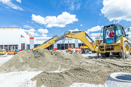 Zrenjanin, Vojvodina, Serbia - June 29, 2015: Yellow excavator is making pile of soil by pulling ground up on heap at construction site, project in progress.
