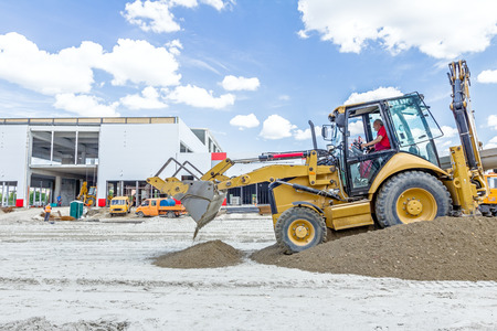 manage transportation: Zrenjanin, Vojvodina, Serbia - June 29, 2015: View on backhoe while he piles up ground at construction site. Editorial