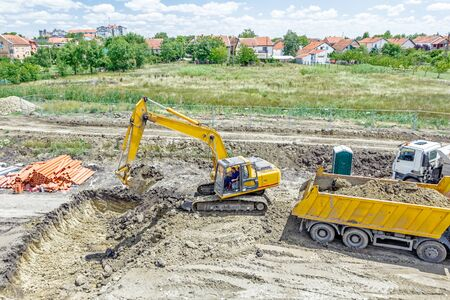 manage transportation: Big excavator is excavating a pit and loading soil into dump truck at construction site, project in progress.