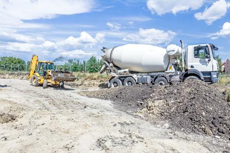 Excavator is transport fresh concrete in his front bucket over building site.