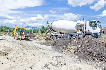 manage transportation: Excavator is transport fresh concrete in his front bucket over building site.