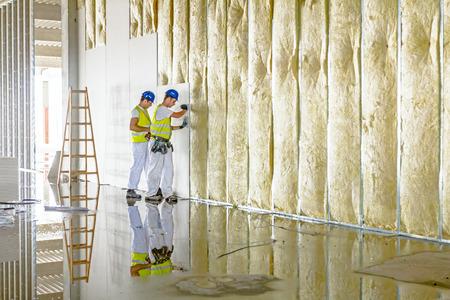 Zrenjanin, 보이 보디 나, 세르비아 - 2015 년 6 월 29 일 : 근로자는 조립식 석고 벽입니다. Plasterboard 건설 나무 사다리를 사용 하여. 에디토리얼