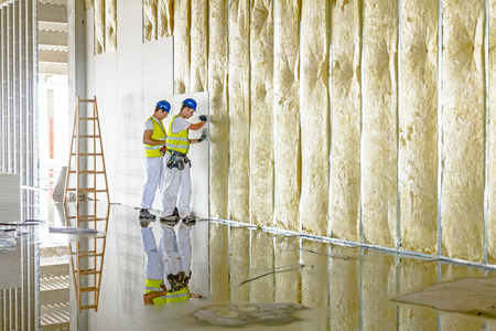 Zrenjanin, Vojvodina, Serbia - June 29, 2015: Workers are assembly gypsum wall. Plasterboard is under construction using wooden ladder.