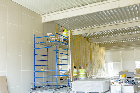 Workers are assembly gypsum wall. Plasterboard is under construction using mobile scaffolding.