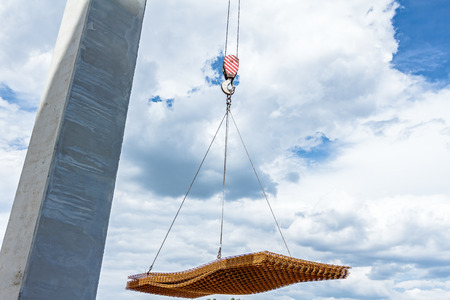 manage transportation: Mobile crane is transport rusty square reinforcement mesh over building site.