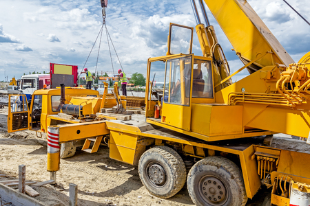Side view on open cabin of the yellow mobile crane with erected long beam. Stock Photo