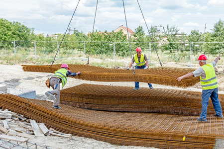 Zrenjanin, Vojvodina, Serbia - June 29, 2015: Team of riggers assist mobile crane to unload reinforcing mesh on pile. Workers are helping in manage the cargo.