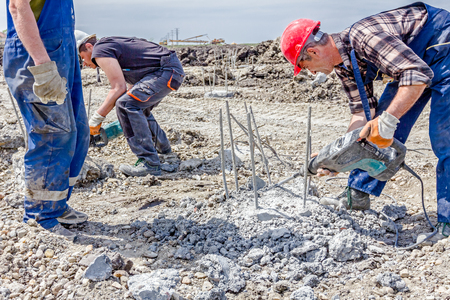 Zrenjanin, Vojvodina, Serbia - April 30, 2015: Constructions workers are using jackhammer to realign reinforced pillars in the ground. Editorial