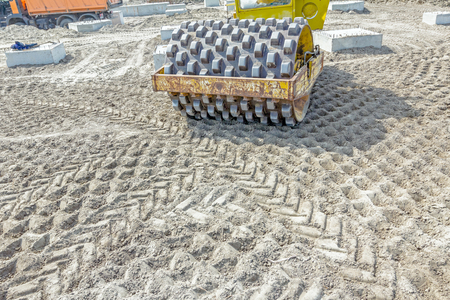 compacting: Construction worker is driving huge road roller with spikes and compacting soil for a large foundation.