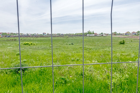 confined: View on the construction site through a fence wire with quadratic shape. Stock Photo