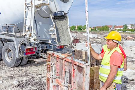 theodolite: Zrenjanin, Vojvodina, Serbia - April 30, 2015: Construction worker is holding leveling rod to help surveyor, geodesist to measure position, depth.