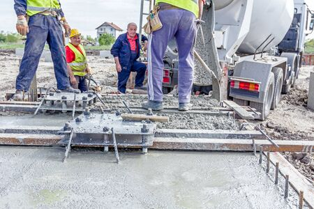 Zrenjanin, Vojvodina, Serbia - April 30, 2015: Workers at building site are pouring concrete in mold from mixer truck. Editorial