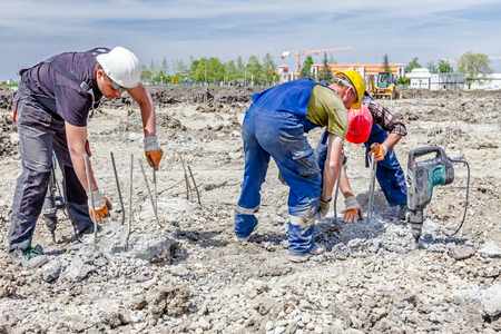 rigger: Zrenjanin, Vojvodina, Serbia - April 30, 2015: Constructions workers are using jackhammer to realign reinforced pillars in the ground. Editorial