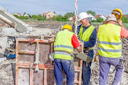 tachymeter: Zrenjanin, Vojvodina, Serbia - April 30, 2015: Construction worker is holding leveling rod to help surveyor, geodesist to measure position, depth.
