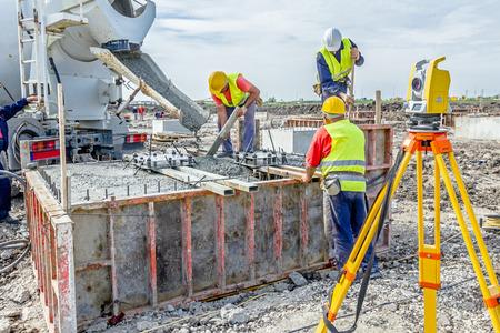 Werknemers op de bouwplaats gieten beton in schimmel van mengwagen.