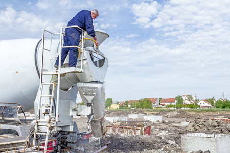 Zrenjanin, Vojvodina, Serbia - April 30, 2015: Driver is washing mixer truck with water jet, after concrete casting.