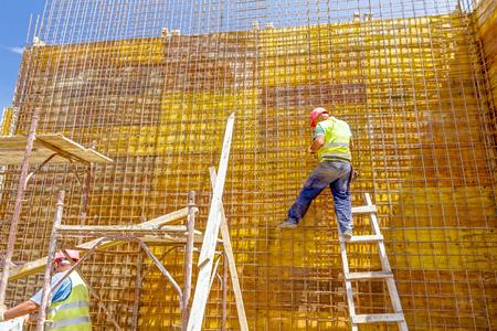 Bouwvakker is bindende betonstaal voor lang gewapend beton constructie op de bouwplaats. Stockfoto