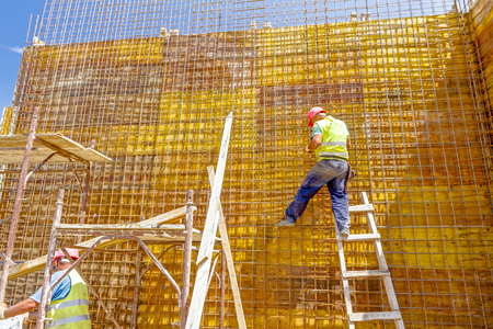 Construction worker is binding rebar for tall reinforced concrete construction at the building site. Stock Photo