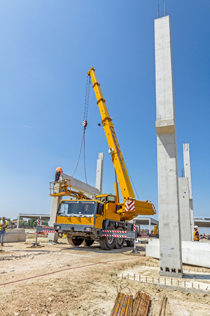 Mobile crane is operating and worker is assembly concrete joist in high place. Height worker is placing truss on building skeleton. Stock Photo