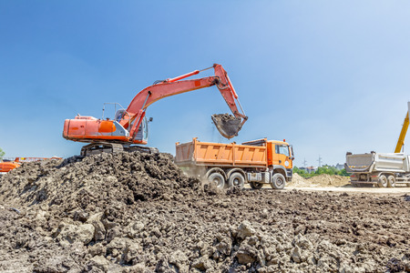 Big excavator is filling a dump truck with soil at construction site, project in progress. Stock Photo