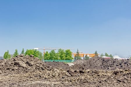 Soil layer on building site, blue sky, ground, wavy piles of earth, dry mud