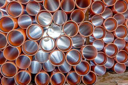 Sewer pipes waiting to be placed into the ditch at construction site.