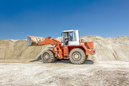 cargador frontal: Red loader with wheels at earthmoving works, he is pushing sand on huge pile, preparing pile of for loading in truck on building site.