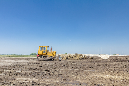 View on heavy bulldozer while he moving, leveling ground at construction site.